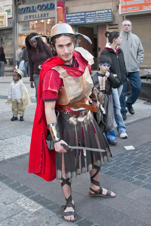 masquerading: JERUSALEM, ISRAEL - MARCH 15, 2006: Purim carnival.  A young man dressed in a suit of a Roman soldier with a sword in his hand. Purim is celebrated annually according to the Hebrew calendar. Purim is the custom of masquerading in costume and the wearing o Editorial