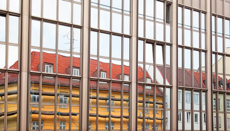 Old building architecture reflected in modern building. Front view of the building. Munich, Germany. photo