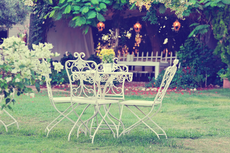 White table and chairs in beautiful garden. Vintage style pictures. photo