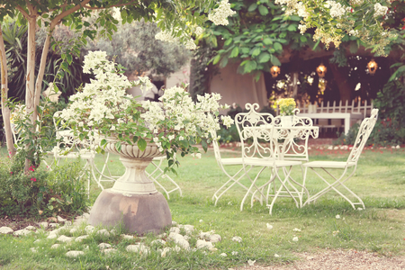 porches: White table and chairs in beautiful garden. Vintage style pictures.