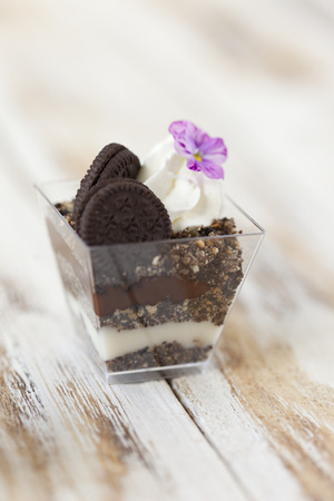 trifle: Trifle black and white chocolate with cookie. Decorated with a flower on old wooden white background. English traditional sweet dessert .