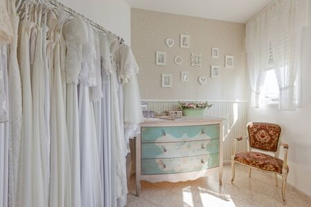 Interior of bridal salon. Beautiful wedding dress on a hangers. In vintage style Stock Photo