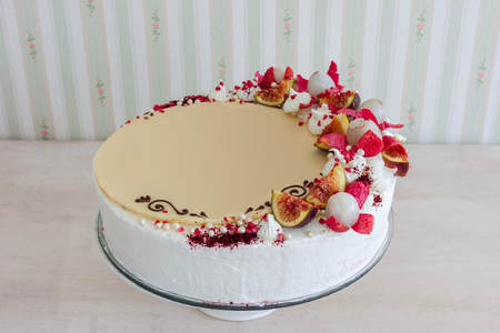 White cake with white chocolate on the wall interior background. Cake decorated with fruits lychees and figs. With blank, place for text.