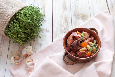카 술레. 고기 돼지 고기 소시지, 거위, 오리 및 때로는 양고기와 흰 콩 두 종류가 들어 있습니다. 프랑스 음식 (요리). 오래 된 목조 흰색 배경에.