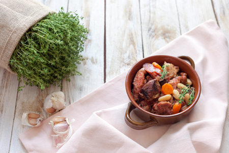 Cassoulet. Containing meat pork sausages, goose, duck and sometimes mutton and two types of white beans. French food (cuisine). On old wooden white background. Banque d'images