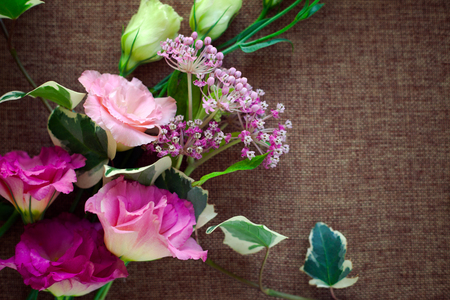 Bouquet beautiful Eustoma flower (Lisianthus, tulip gentian, eustomas) on sacking canvas texture background.