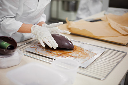 Making chocolate. Making chocolate easter eggs. Chocolate factory. Stock Photo