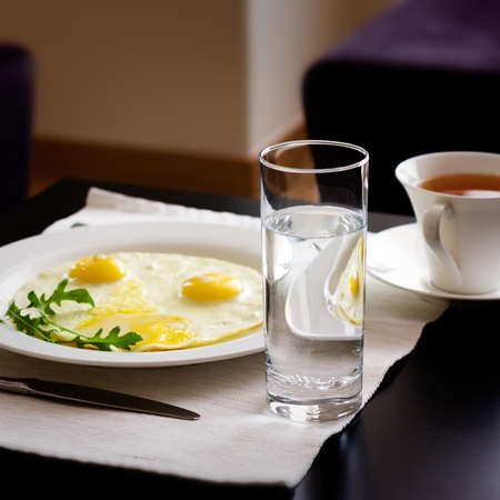 A glass of water, fried eggs and a cap of tee on the table photo