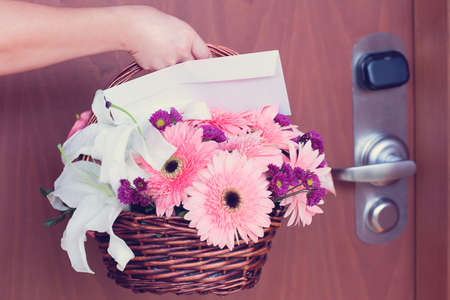 Ein Blumen busket an der Tür durchgeführt Standard-Bild - 28261279