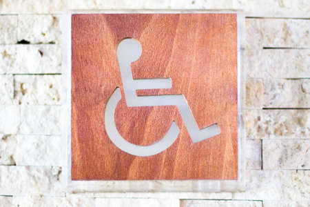 A handicapped sign of wood and glass on a stone wall. Shallow DOF photo