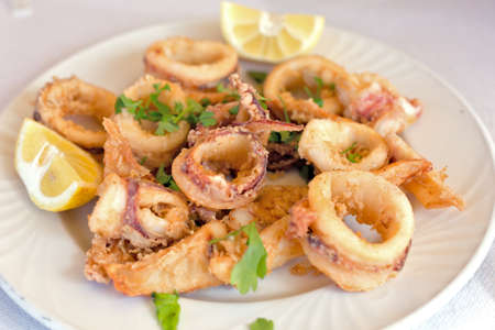 A plate of fresh fried calamary rings with lemon