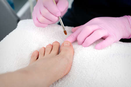 A salon specialist makes pedicure for a young woman photo