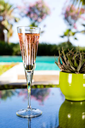 Glass of champagne on the glass table in outdoor resort bar photo