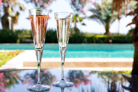 engagement party: Glass of champagne on the glass table in outdoor resort bar