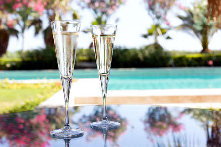 Glass of champagne on the glass table in outdoor resort bar