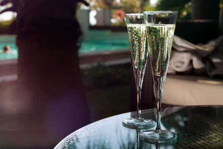 Two glasses of champagne on the glass table on black background photo