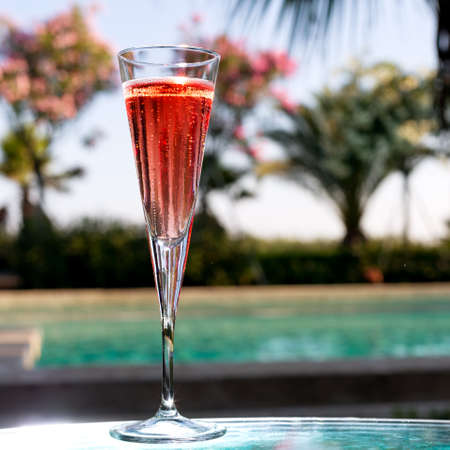 Glass of Kir Royal on the glass table in outdoor resort bar photo