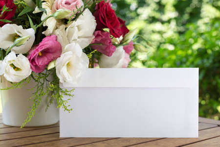 envelope: Envelope and flower bouquet on the wooden table Stock Photo