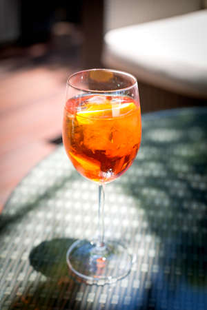 spritz: Glass of Aperol Spritz cocktail on the glass table in outdoor resort bar