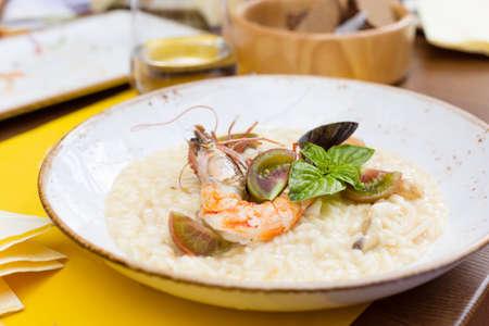 Seafood risotto met garnalen, tomaten en basilicum in het restaurant