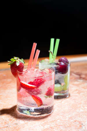 Two glasses of strawberry and grape mojitoes on marble table