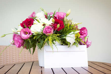 fresh flowers: Envelope and flower bouquet on the wooden table Stock Photo
