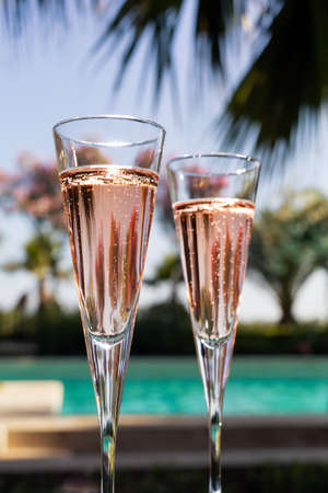 Two glasses of champagne on the glass table in outdoor resort bar Imagens - 33459715