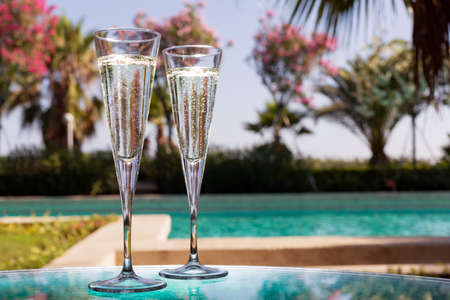 Two glasses of champagne on the glass table in outdoor resort bar photo