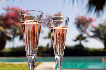 Two glasses of champagne on the glass table in outdoor resort bar