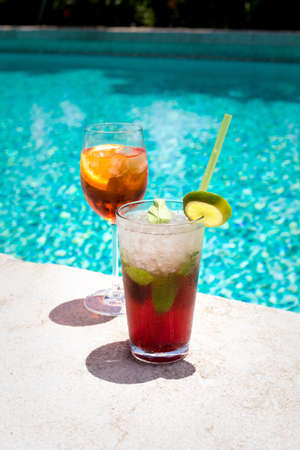 pool bar: Two glasses of Aperol Spritz and Mojito Royal cocktails on the swimming pool nosing