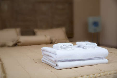 bright housekeeping: White towels piled on the hotel bed Stock Photo
