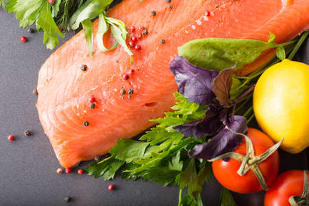 Raw salmon on a pan with salad, tomato and lemon Stock Photo