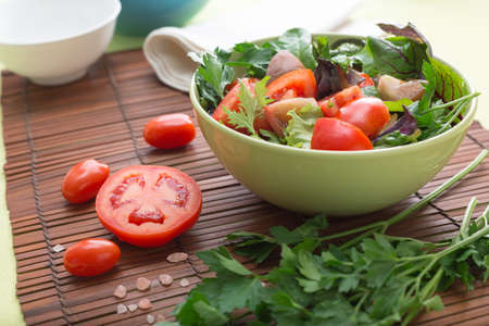 A bowl of green salad with tomatoes