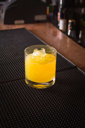alcohol screwdriver: Screw driver cocktail on a bar ribber mat on dark background. Shallow DOF