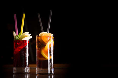 Cherry bomb and cuba libre cocktails in a tall glasses on the dark background. Shallow DOF Imagens