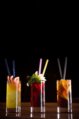 alcohol screwdriver: Cherry bomb, screwdriver and cuba libre cocktails in a tall glasses on the dark background. Shallow DOF