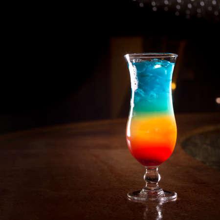 rainbow cocktail: Arcobaleno cocktail sulla barra stand con sfondo scuro. Shallow DOF