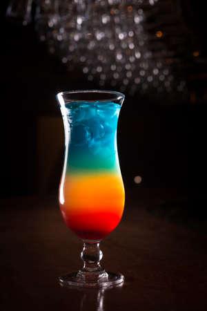 rainbow cocktail: C�ctel del arco iris en la barra de pie con fondo oscuro. DOF bajo Foto de archivo