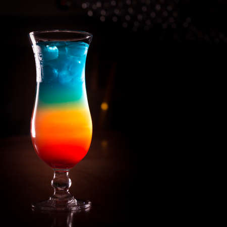 rainbow cocktail: Rainbow cocktail on the bar stand with dark background. Shallow DOF and marsala tonned Stock Photo