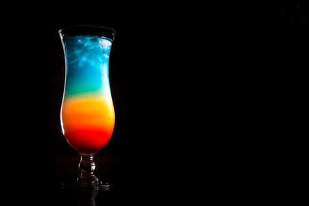 rainbow cocktail: Rainbow cocktail on the bar stand with dark background. Shallow DOF