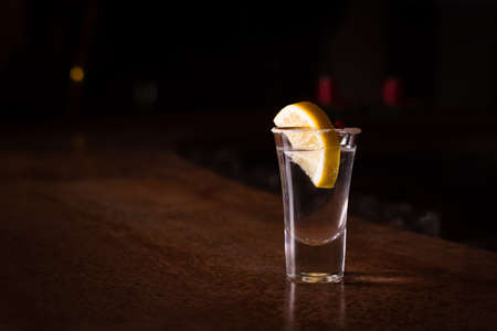 Tequila shot with lemon on the dark background. Shallow DOF