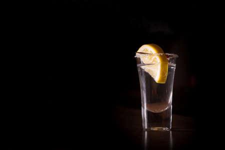 shot: Tequila shot with lemon on the dark background. Shallow DOF