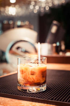White russian cocktail on the bar stand on rubber mat. Shallow DOF and marsala tonned
