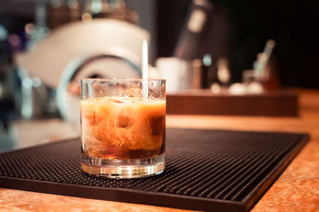 White russian cocktail on the bar stand on rubber mat. Shallow DOF and marsala tonned Imagens - 37101565