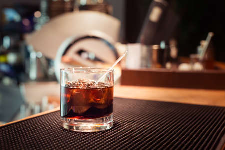 Black russian cocktail on the bar stand on rubber mat. Shallow DOF and marsala tonned