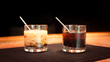 Black russian and white russian cocktails on the bar stand on rubber mat. Shallow DOF and marsala tonned