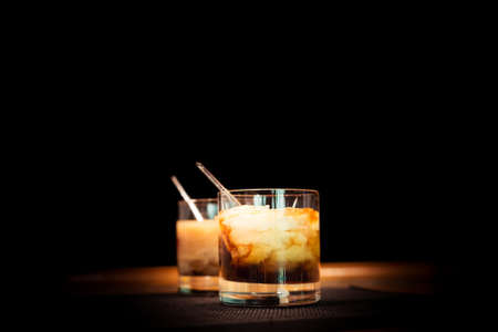 bartender: Two white russian cocktails on the bar stand on rubber mat. Shallow DOF and marsala tonned Stock Photo