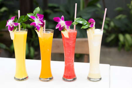 Tropical fresh juices with orchids in an outdoor restaurant. Shallow DOF photo