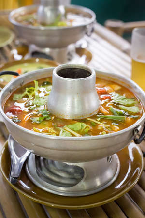 gung: Tom yum soup in traditional dishware in a street restaurant