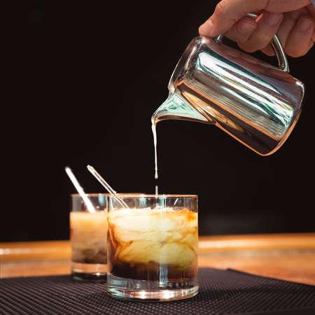 Vorbereitung der weißen russische Cocktails an der Bar Zähler auf Gummimatte. Shallow DOF und Marsala tonned Standard-Bild - 37751399
